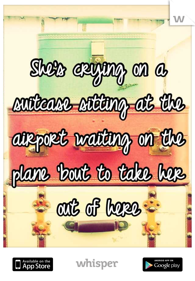 She's crying on a suitcase sitting at the airport waiting on the plane 'bout to take her out of here