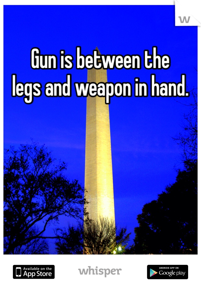 Gun is between the  legs and weapon in hand.