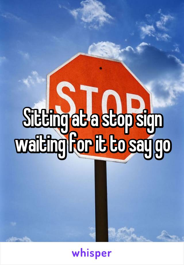 Sitting at a stop sign waiting for it to say go