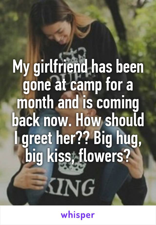 My girlfriend has been gone at camp for a month and is coming back now. How should I greet her?? Big hug, big kiss, flowers?