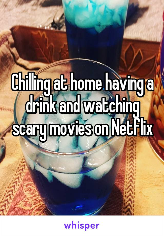Chilling at home having a drink and watching scary movies on Netflix