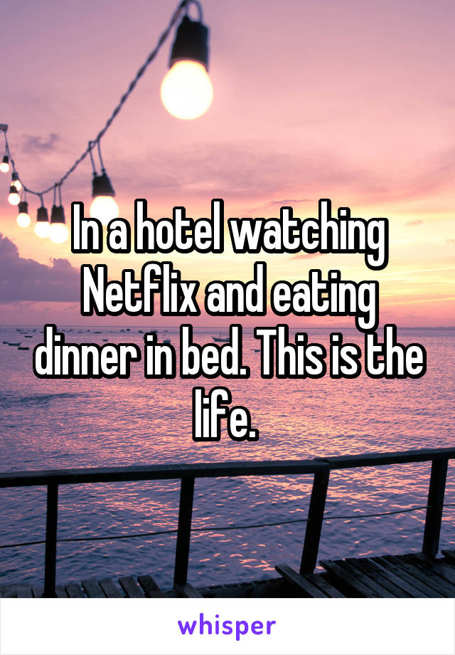 In a hotel watching Netflix and eating dinner in bed. This is the life.