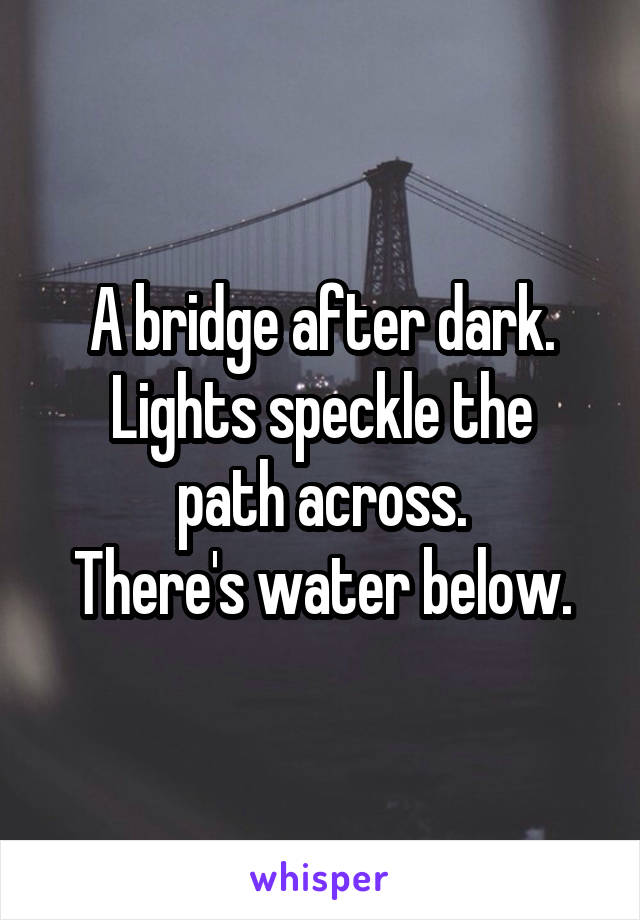 A bridge after dark. Lights speckle the path across. There's water below.
