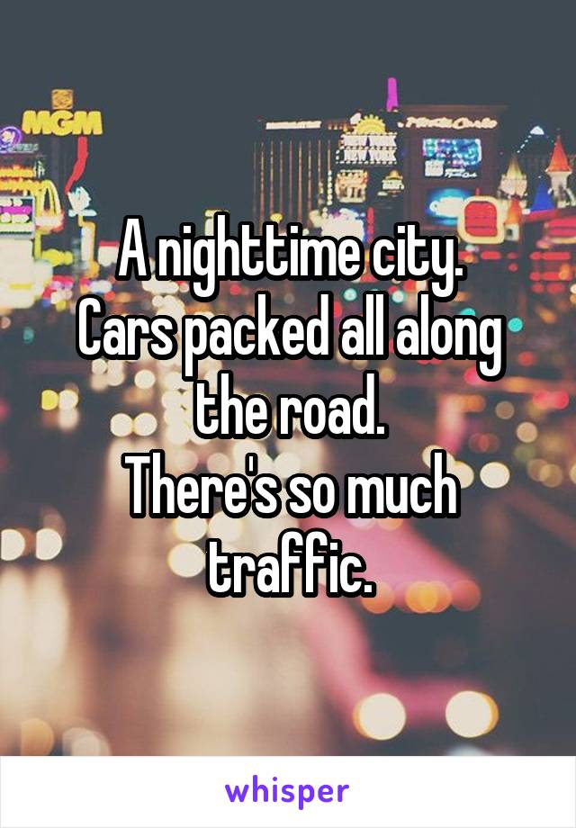 A nighttime city. Cars packed all along the road. There's so much traffic.