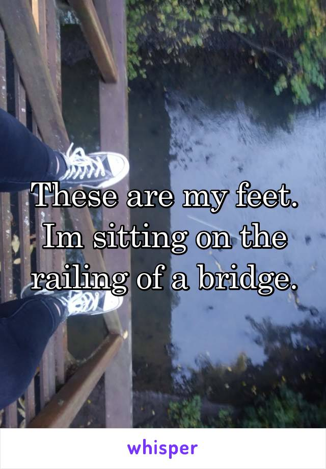 These are my feet. Im sitting on the railing of a bridge.