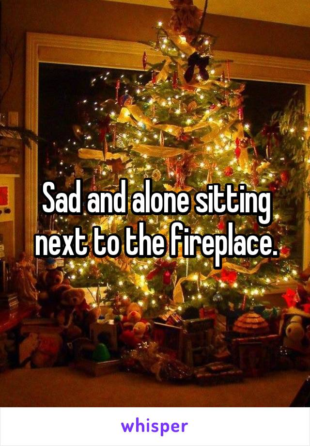 Sad and alone sitting next to the fireplace.