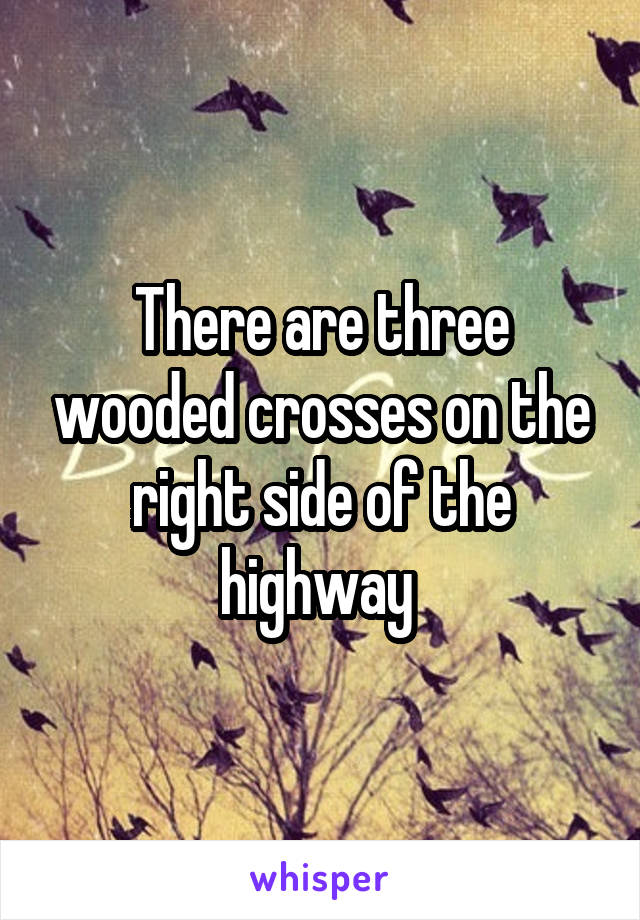 There are three wooded crosses on the right side of the highway